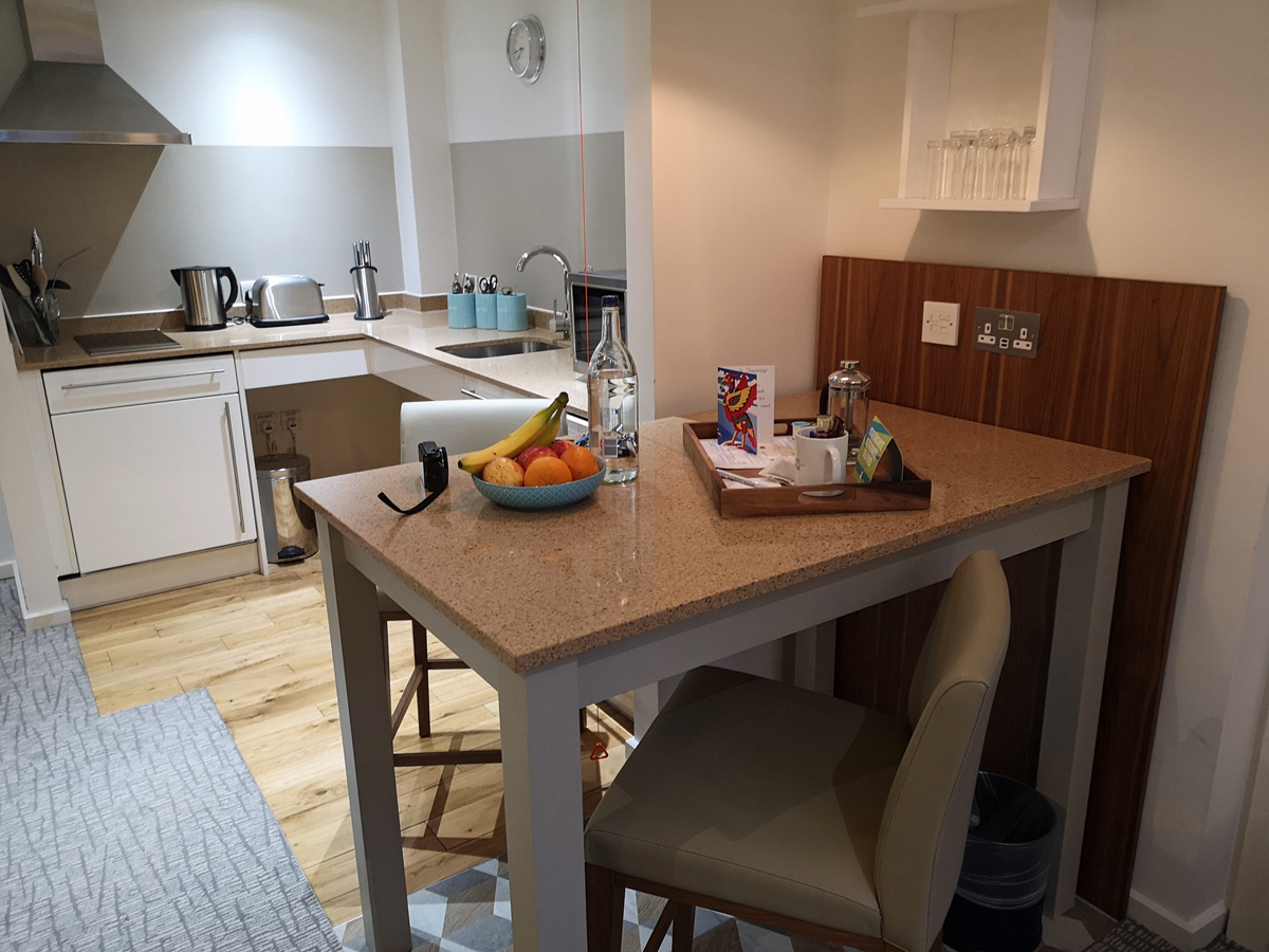 A close up of the breakfast bar/work desk with a fruit bowl, tea/coffee supplies and a glass water bottle.