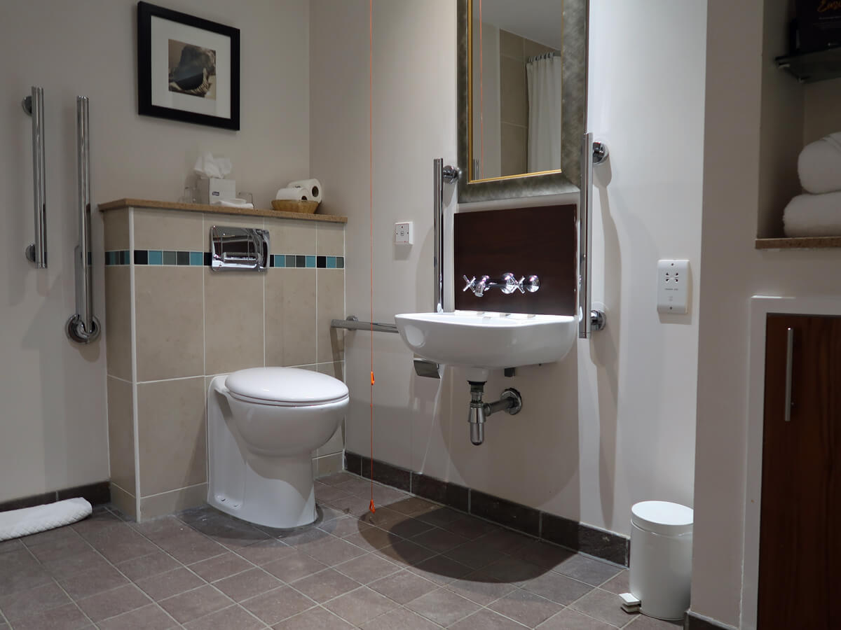 The toilet and wash basin sink in the wheelchair accessible bathroom.