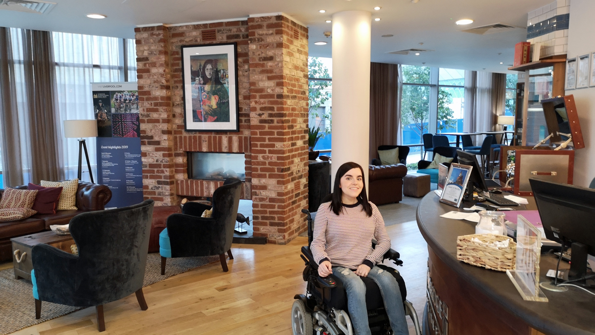Emma in her wheelchair sitting next to the reception desk checking in. Emma is smiling.