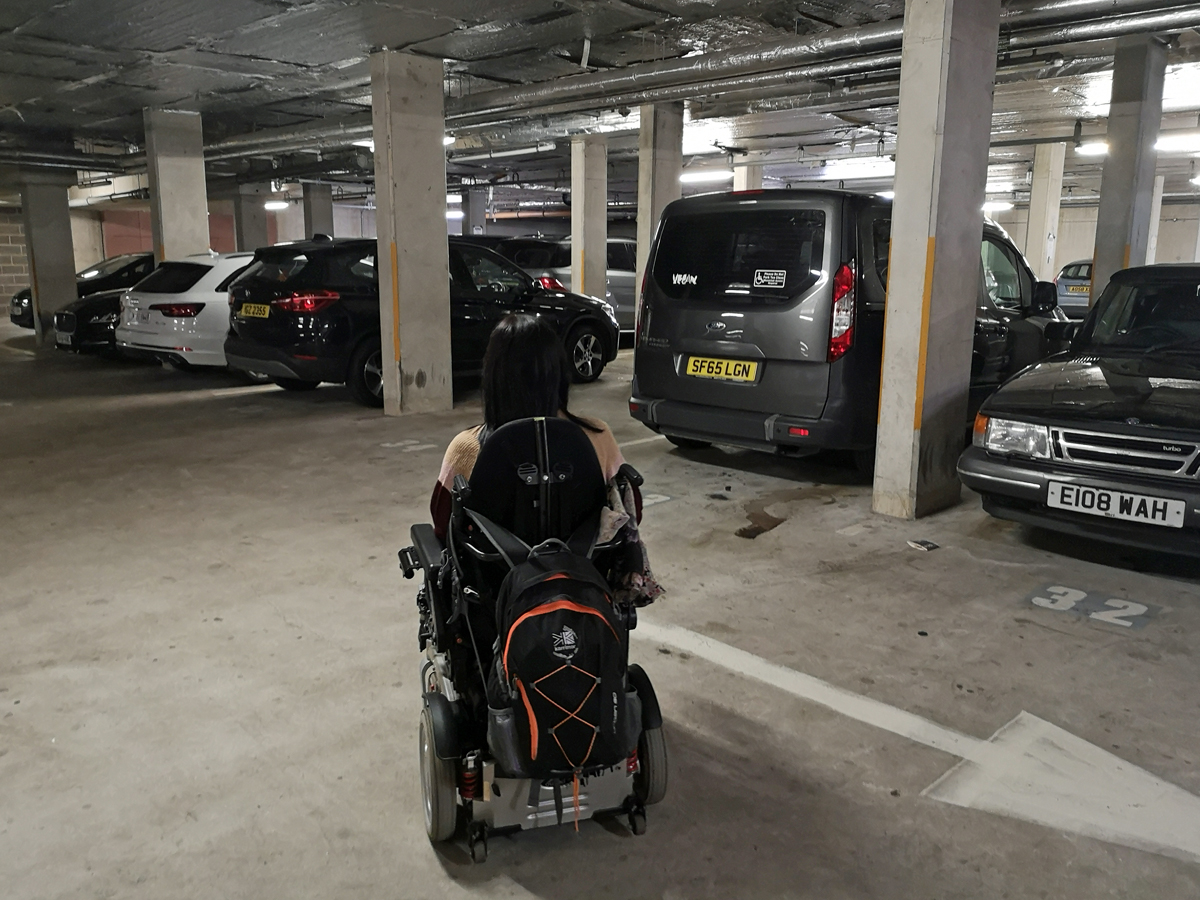 Emma beside her car in the undercover hotel car park garage.