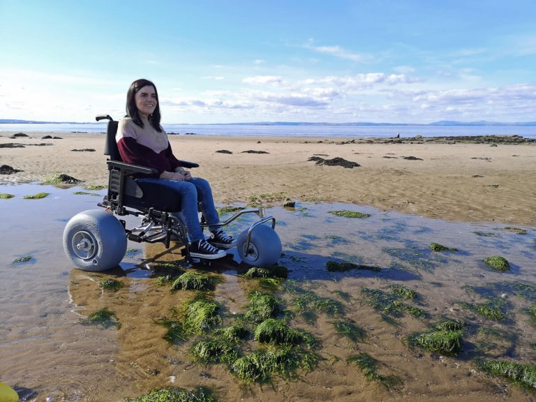 Emma sitting in the WheelEEZ® Beach Wheelchair Conversion Kit.