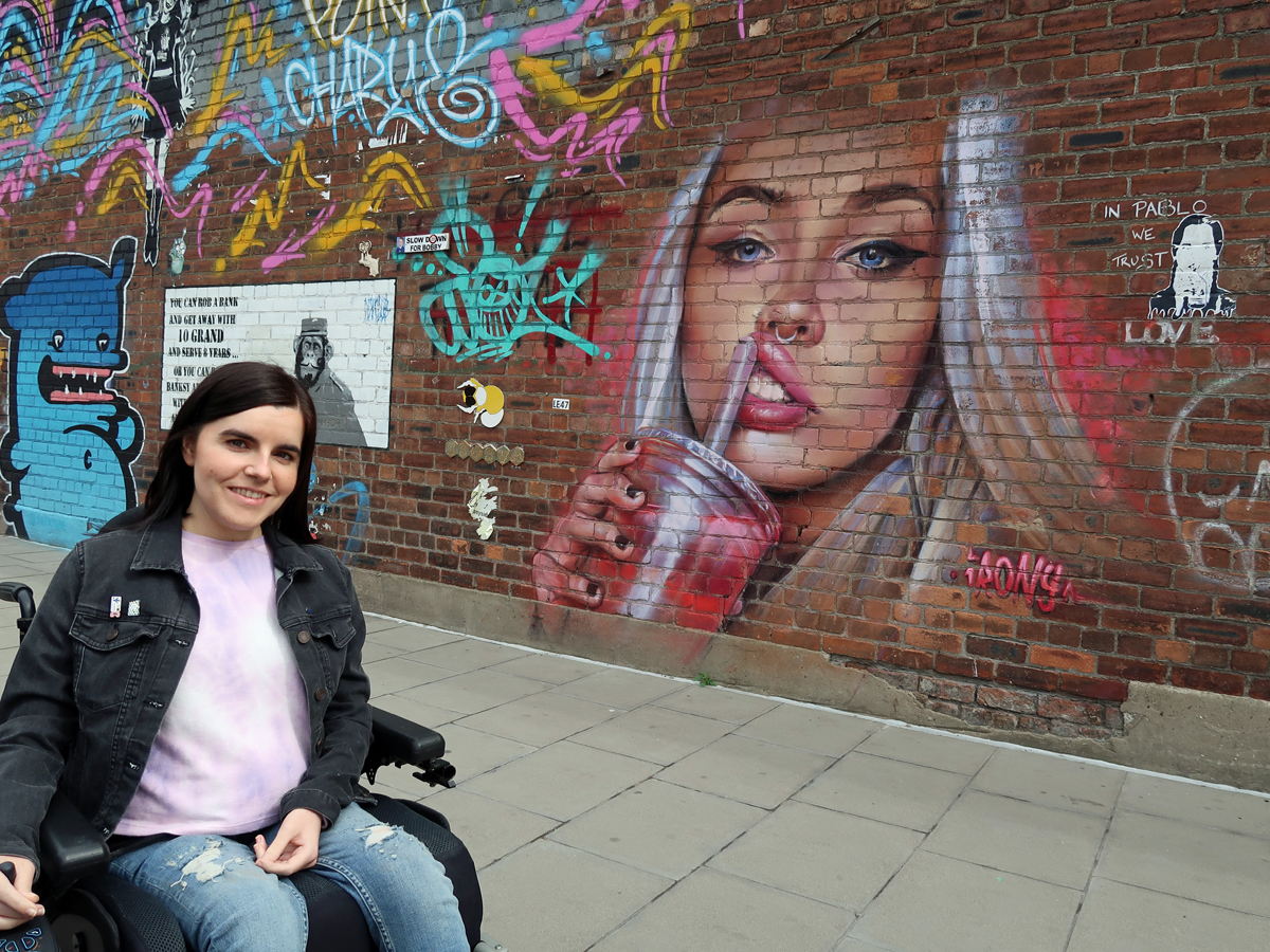 Emma sitting in her wheelchair next to a wall covered in street artwork.