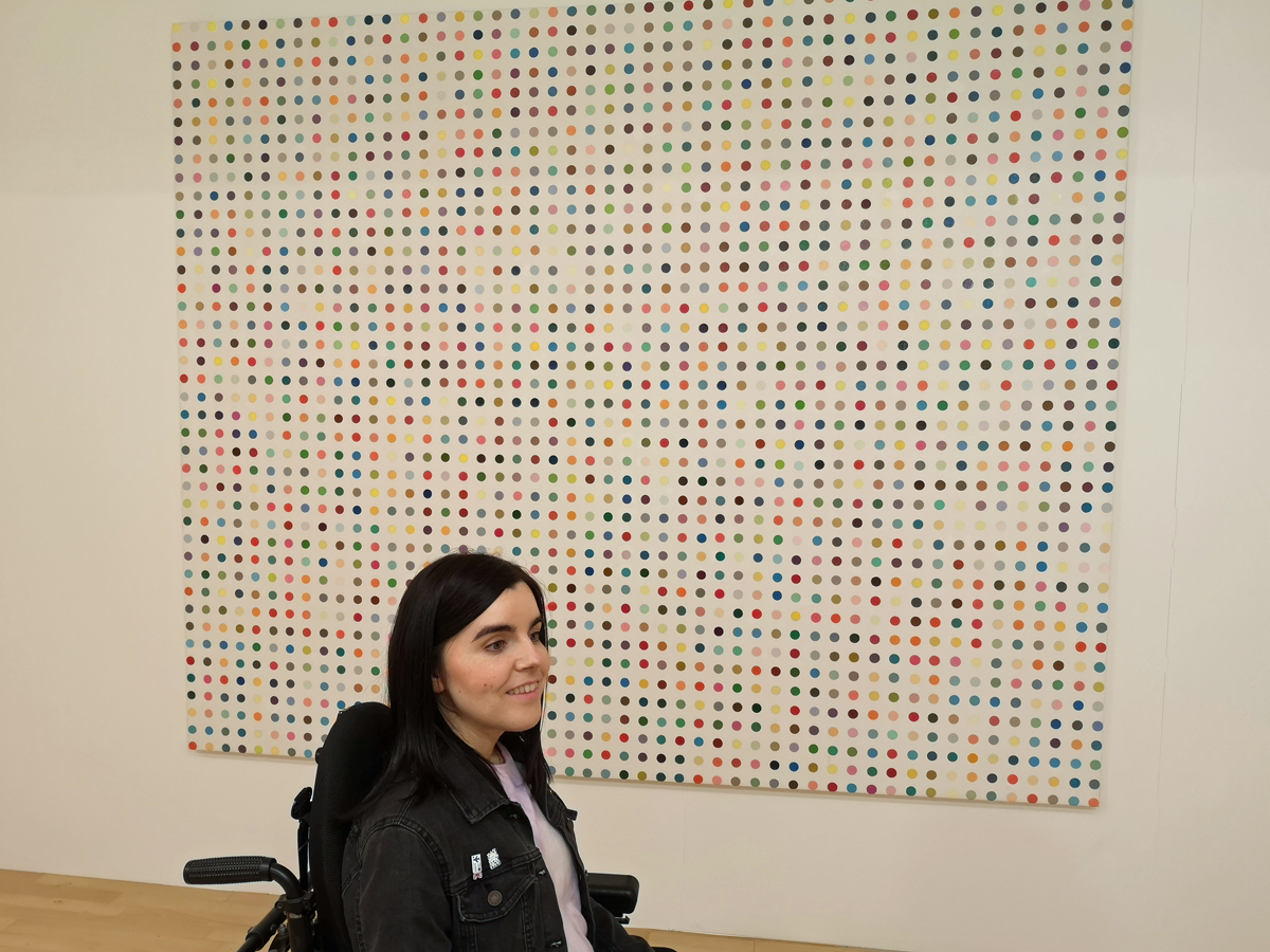 Emma sitting in front of the Damien Hirst dot painting at Tate Liverpool.