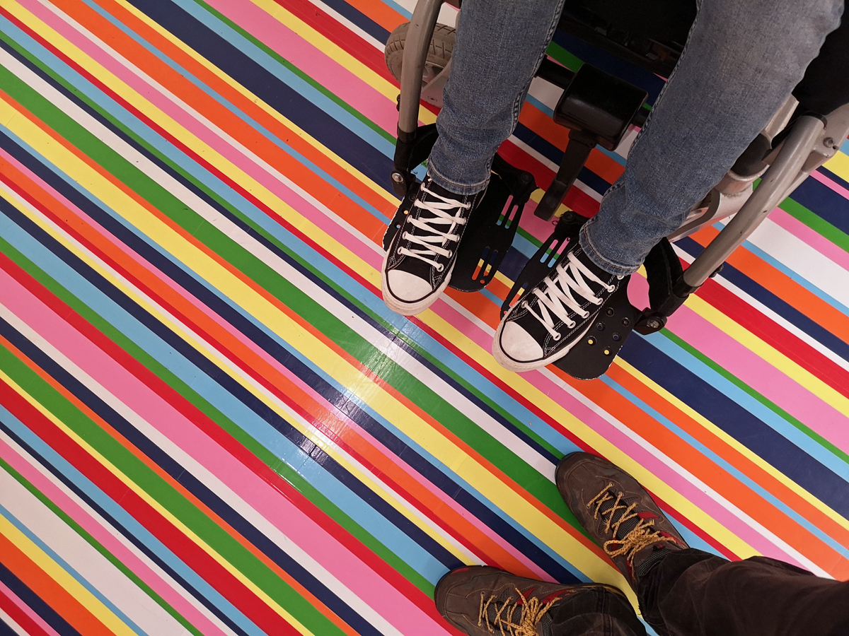 A view looking down at Emma's legs and feet on her wheelchair plates and Allans shoes on a multicolored striped floor.