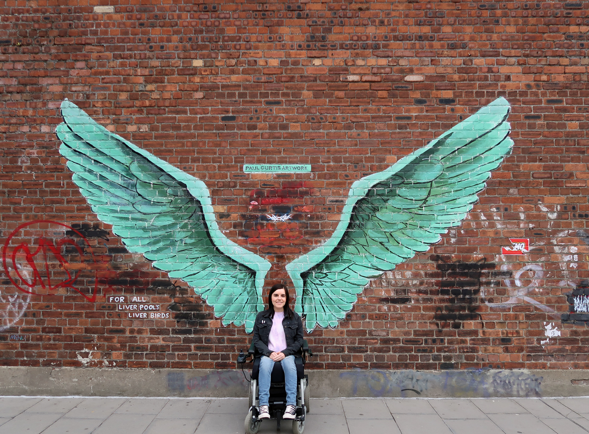 Emma sitting in her wheelchair infront of the Paul Curtis Liver Birds Wings.