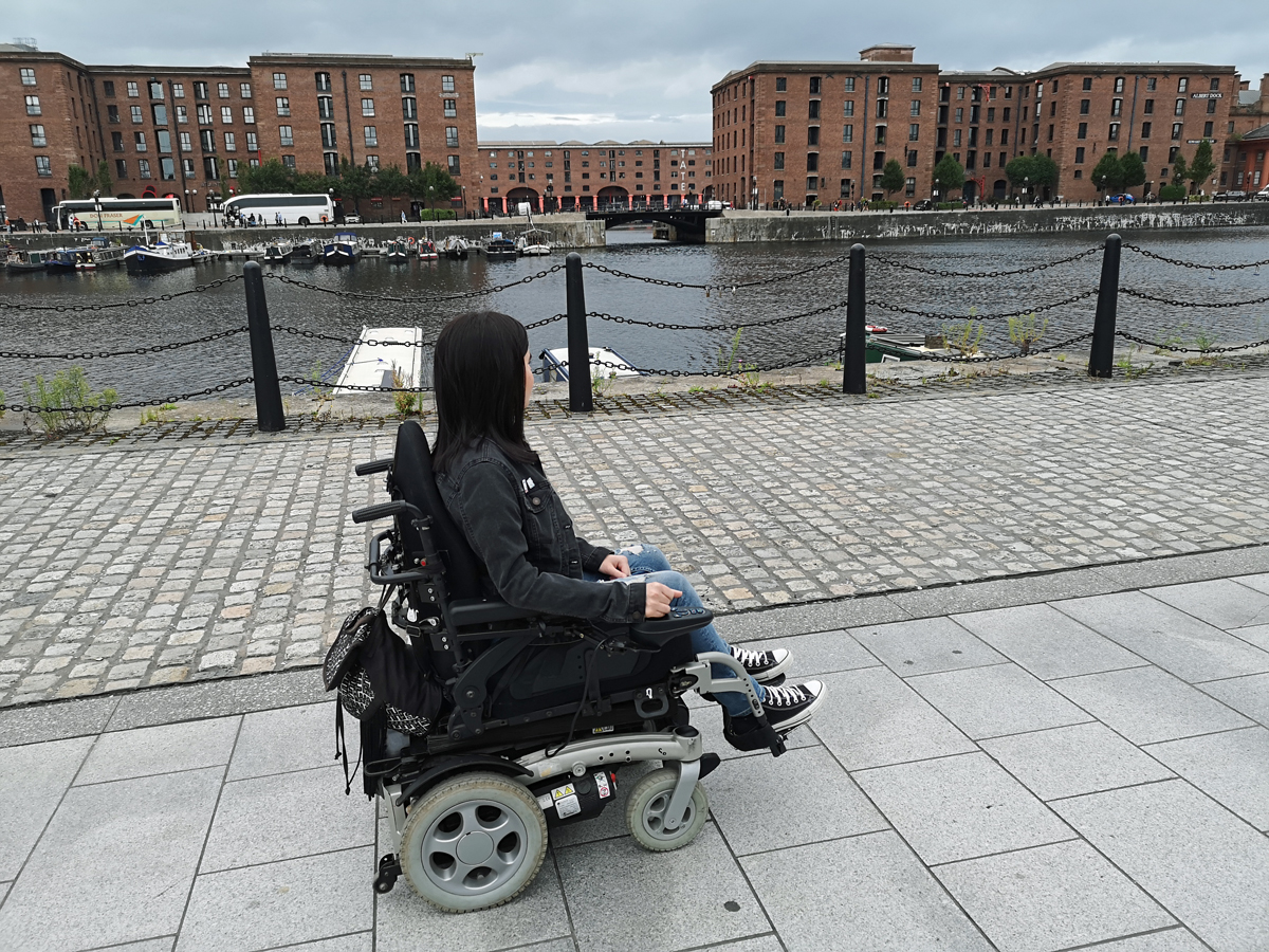 Emma driving her wheelchair along Albert Dock Liverpool.