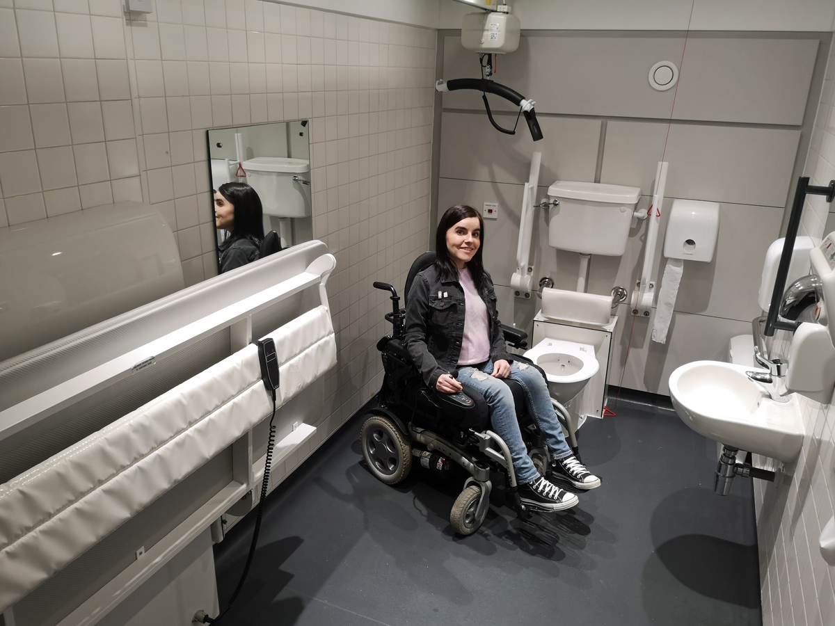 Emma sitting inside the Tate Liverpool Changing Places toilet.