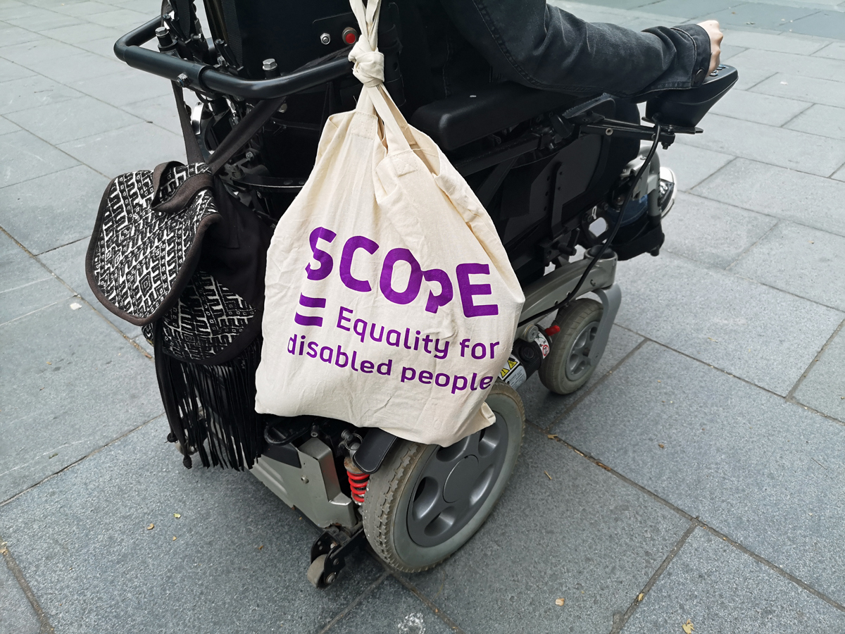 "A canvas shopping bag hanging on the back of Emma's wheelchair. The bag is from the charity Scope with the words ""Equality for Disabled People"""