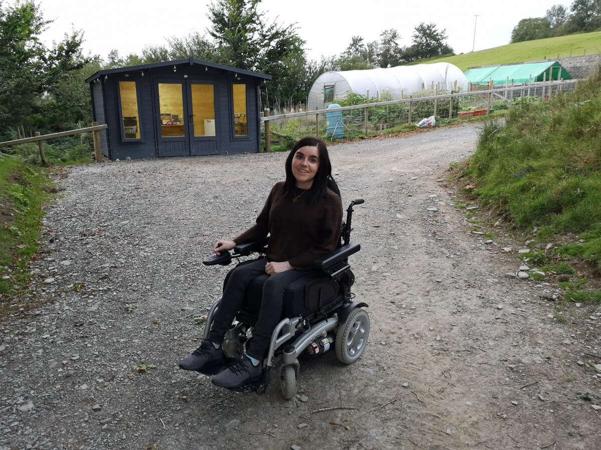 Emma sitting in her wheelchair outside in front of the onsite honesty shop.