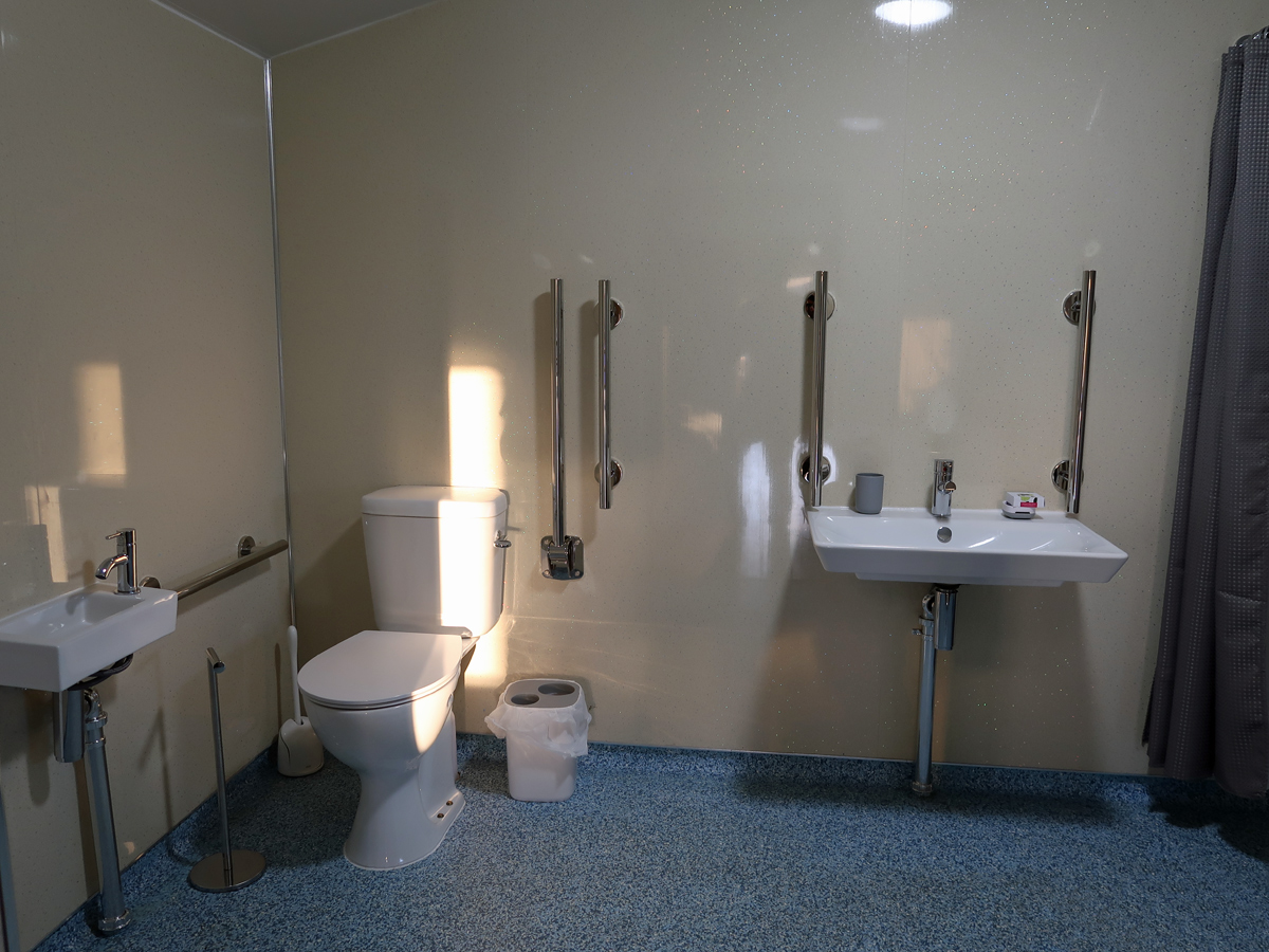 The accessible bathroom in the accessible safari ten showing the toilet and roll-under sink.