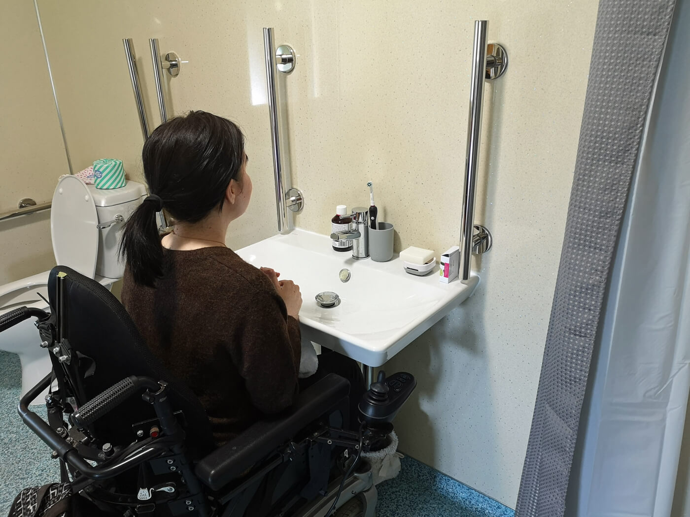 Emma sitting in her wheelchair at the roll-under bathroom sink.