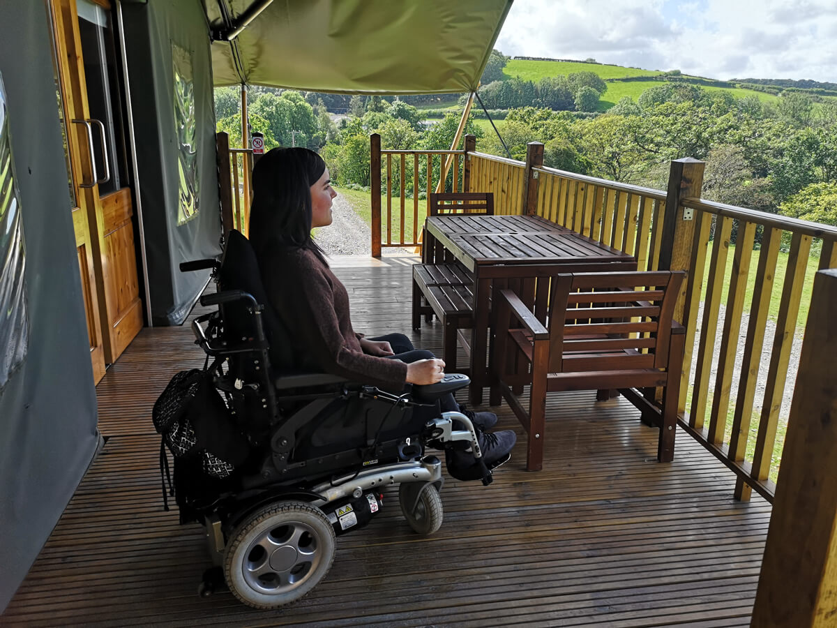 Emma sitting in her wheelchair on the decking looking out at the view.