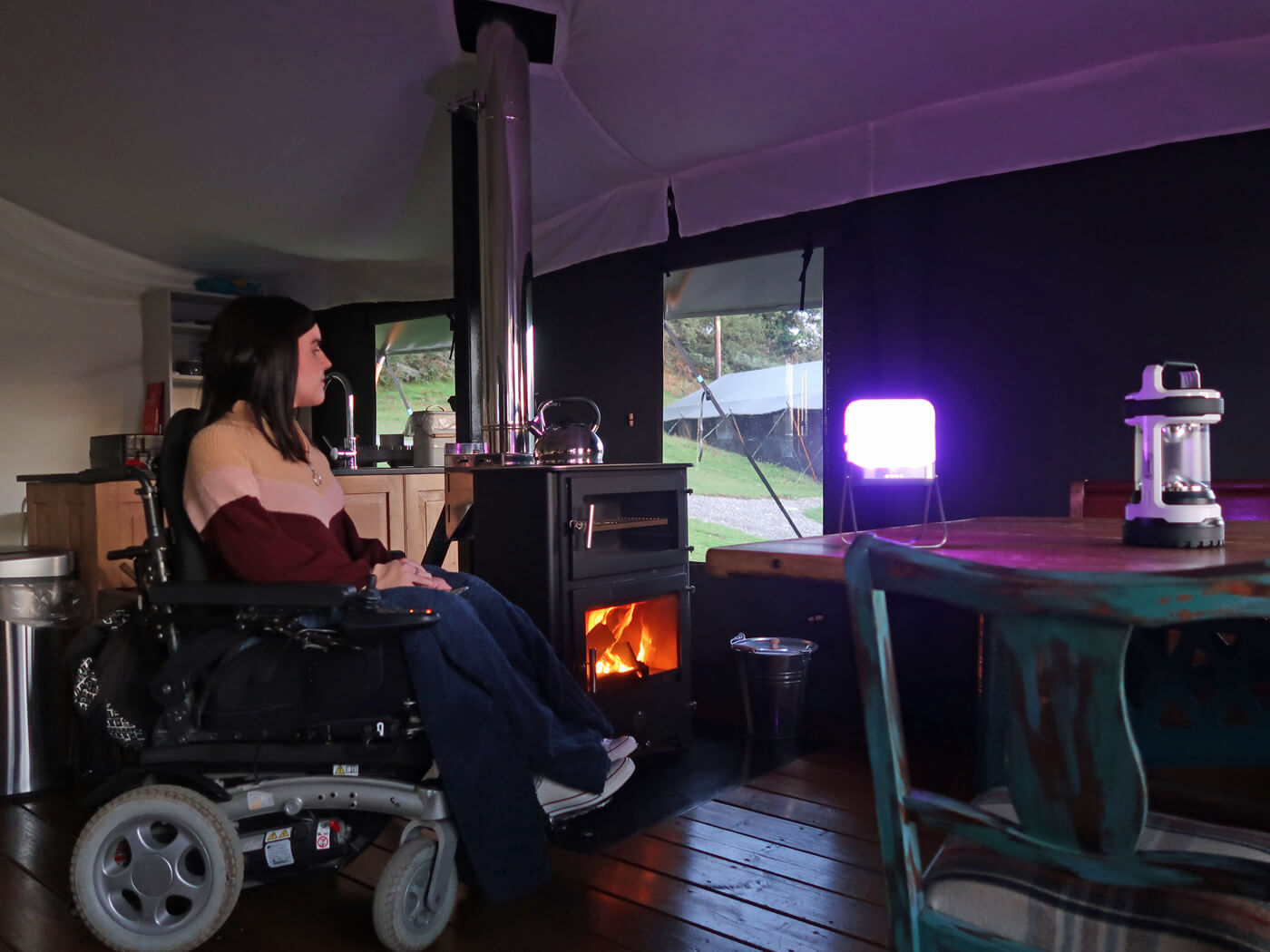 Emma sitting in her wheelchair next to the log fire in the safari tent.
