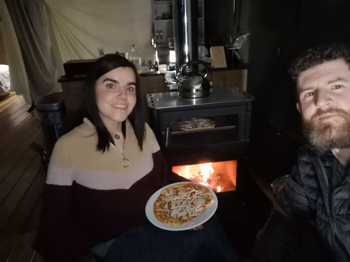 Emma and Allan sitting next to the log burner holding a plate with a freshly baked pizza.