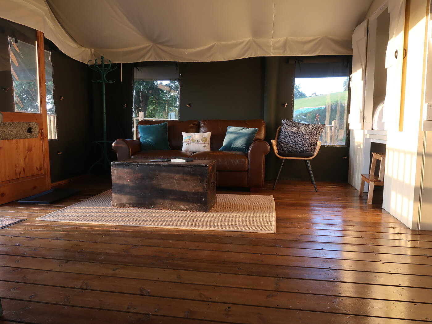 The lounge in our wheelchair accessible safari tent. The golden sun is streaming through the open sliding doors, casting beautiful golden light into the lounge.