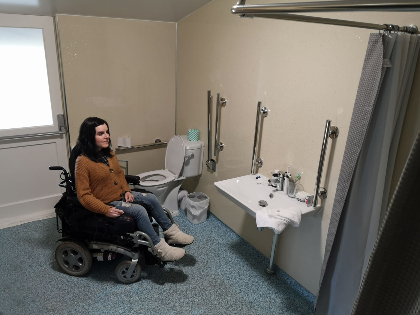 Emma sitting in her wheelchair in the accessible safari tent bathroom