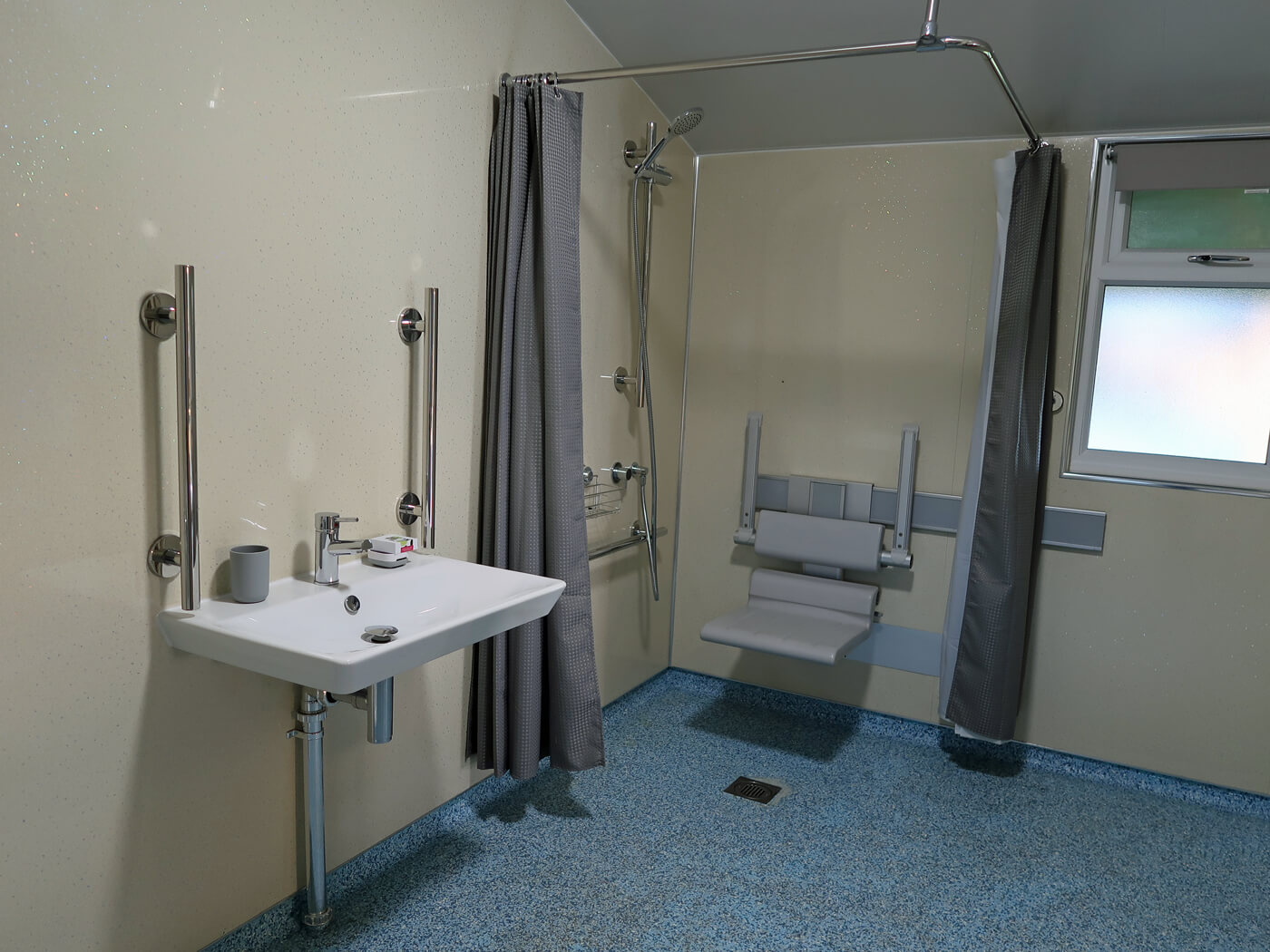 The accessible bathroom in the accessible safari ten showing the sink and roll-in shower.