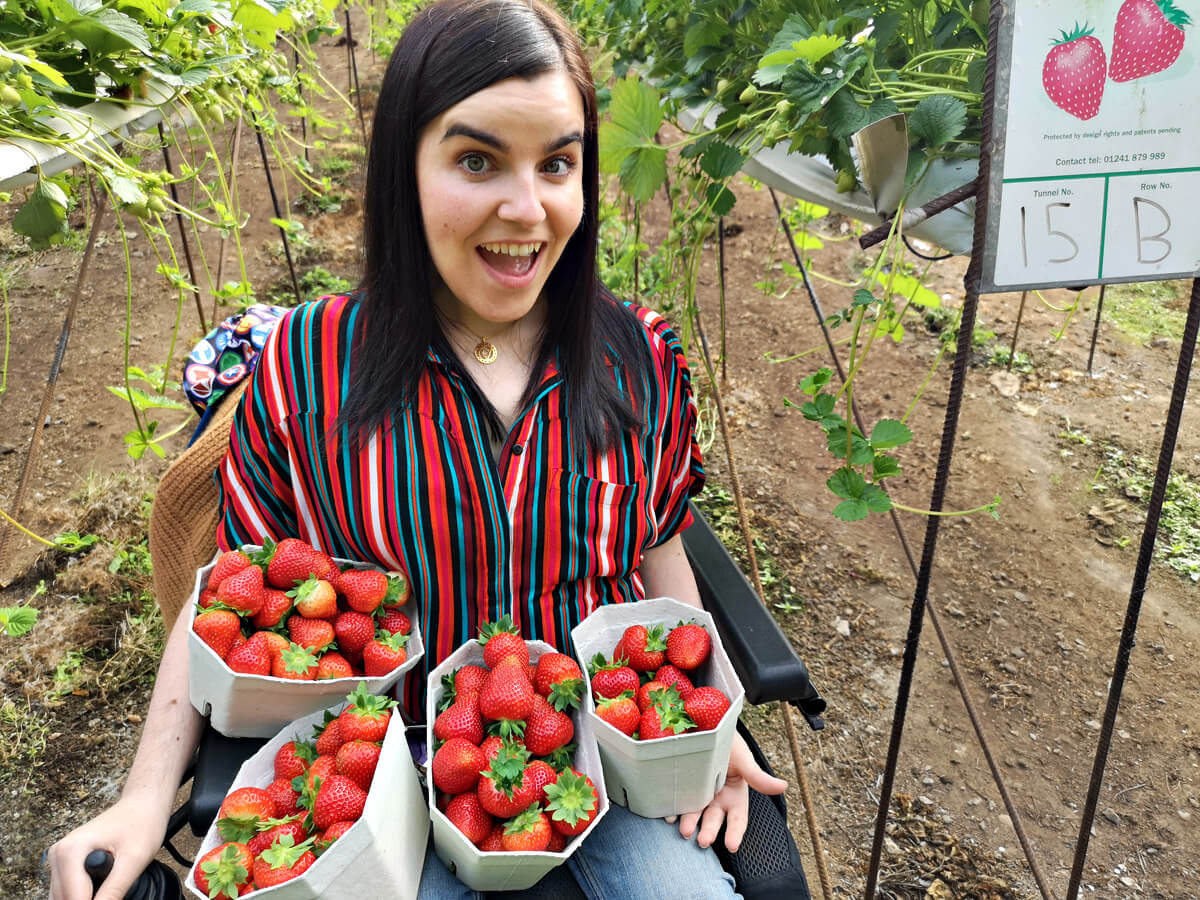 Emma looking shocked while holding four tubs of strawberries on her lap.