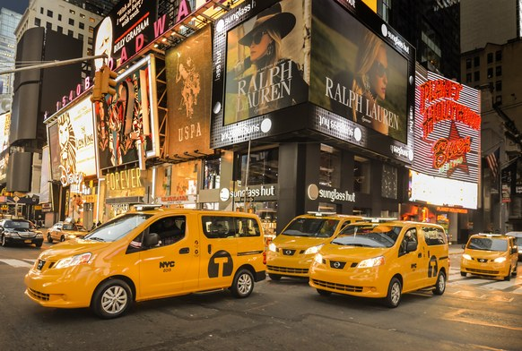 Several accessible yellow taxis driving through Times Square in New York City at night.