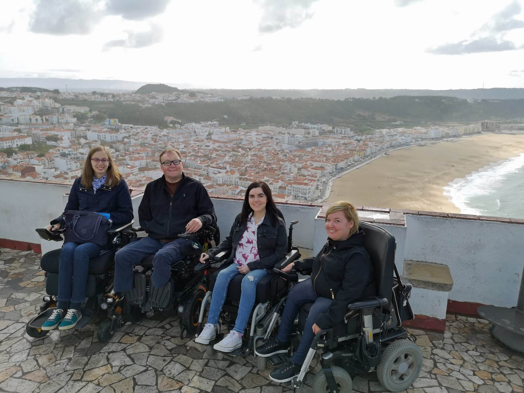 Emma with John Morris, Sanna and Blandine, a group of accessible travel bloggers. They are sitting in their wheelchairs with the Nazaré beach behind them.