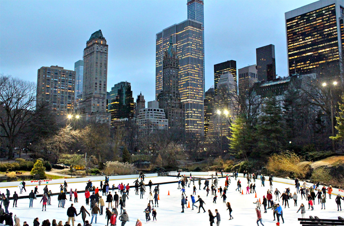 A view overlooking the Wollman Rink in Central Park, New York. The buildings are lit up in the background and people are skating on the ice rink below.