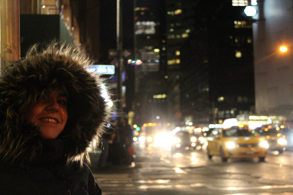 A close up shot of Emma from the shoulders up. She has her huge furry hood up. The busy New York traffic is behind her including a yellow cab.