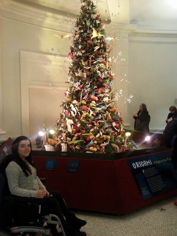 Emma inside the American Museum of Natural History. She is sitting next to a Christmas tree decorated in origami.