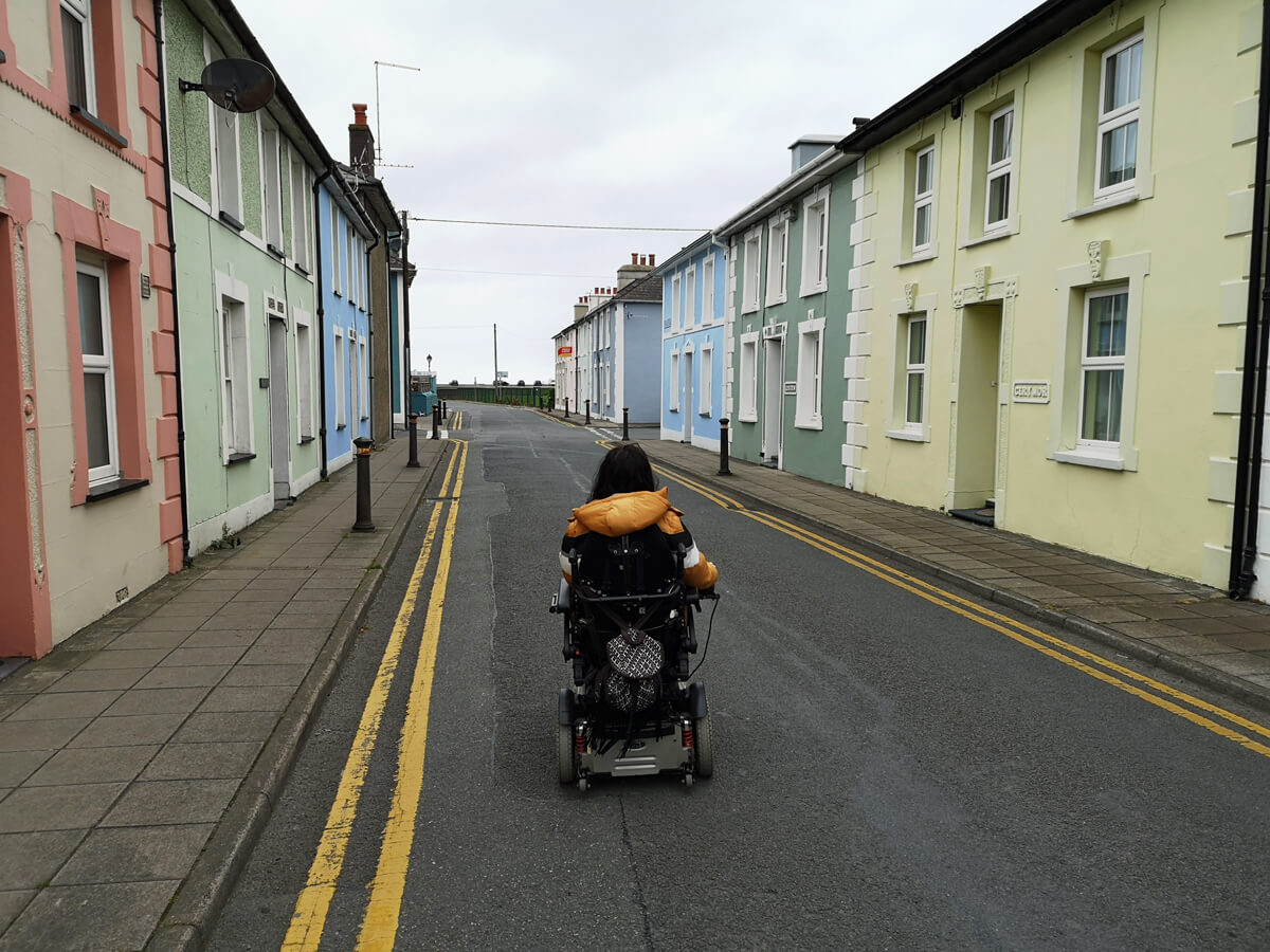 Emma driving down the middle of a street of colourful homes in Aberaeron.