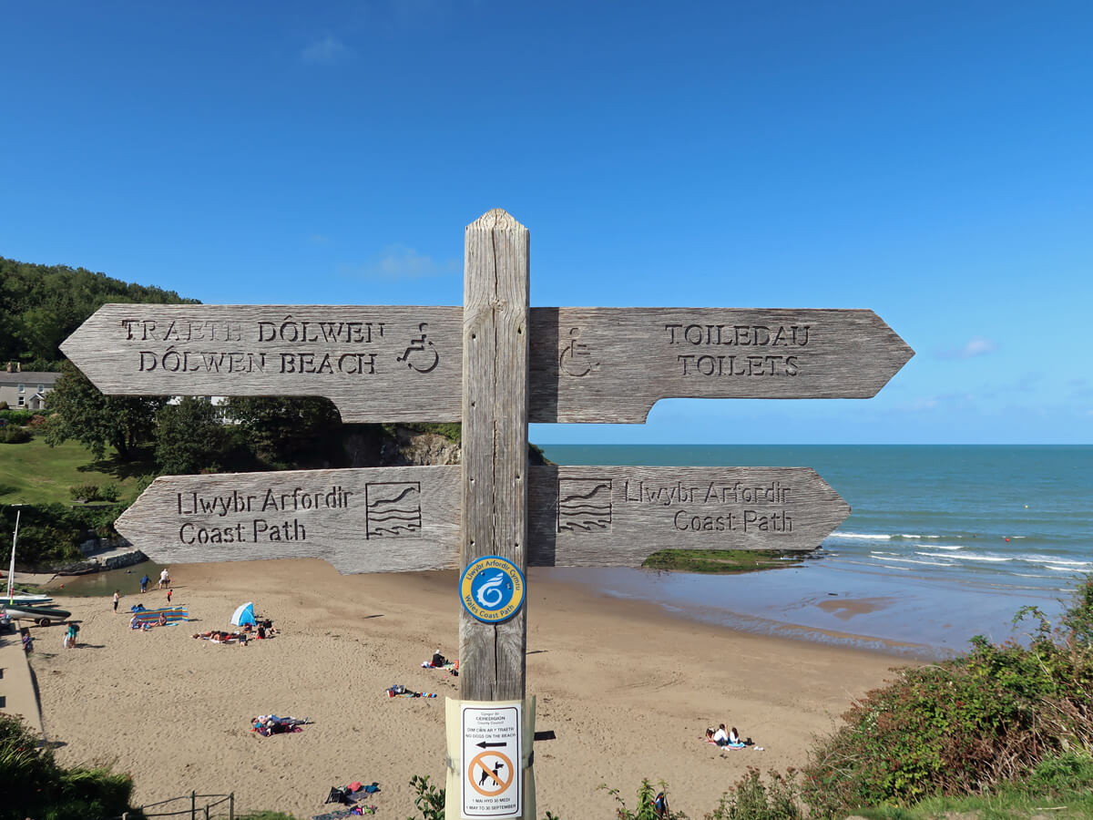A wooden sign with directions to the accessible toilets etc with the beach in the background.