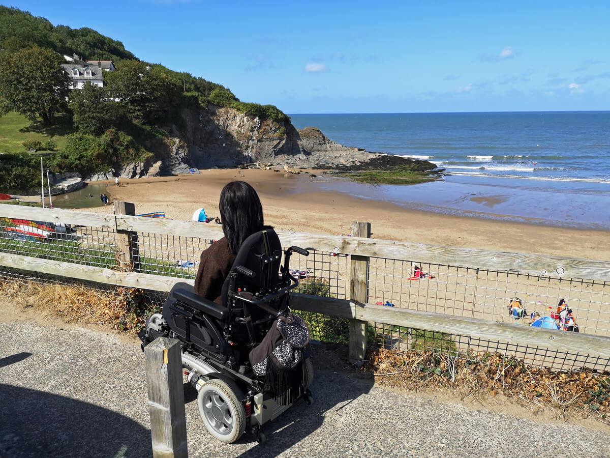 Emma in her wheelchair sitting at the top of the cliff overlooking Aberporth Beach on a clear sunny day.