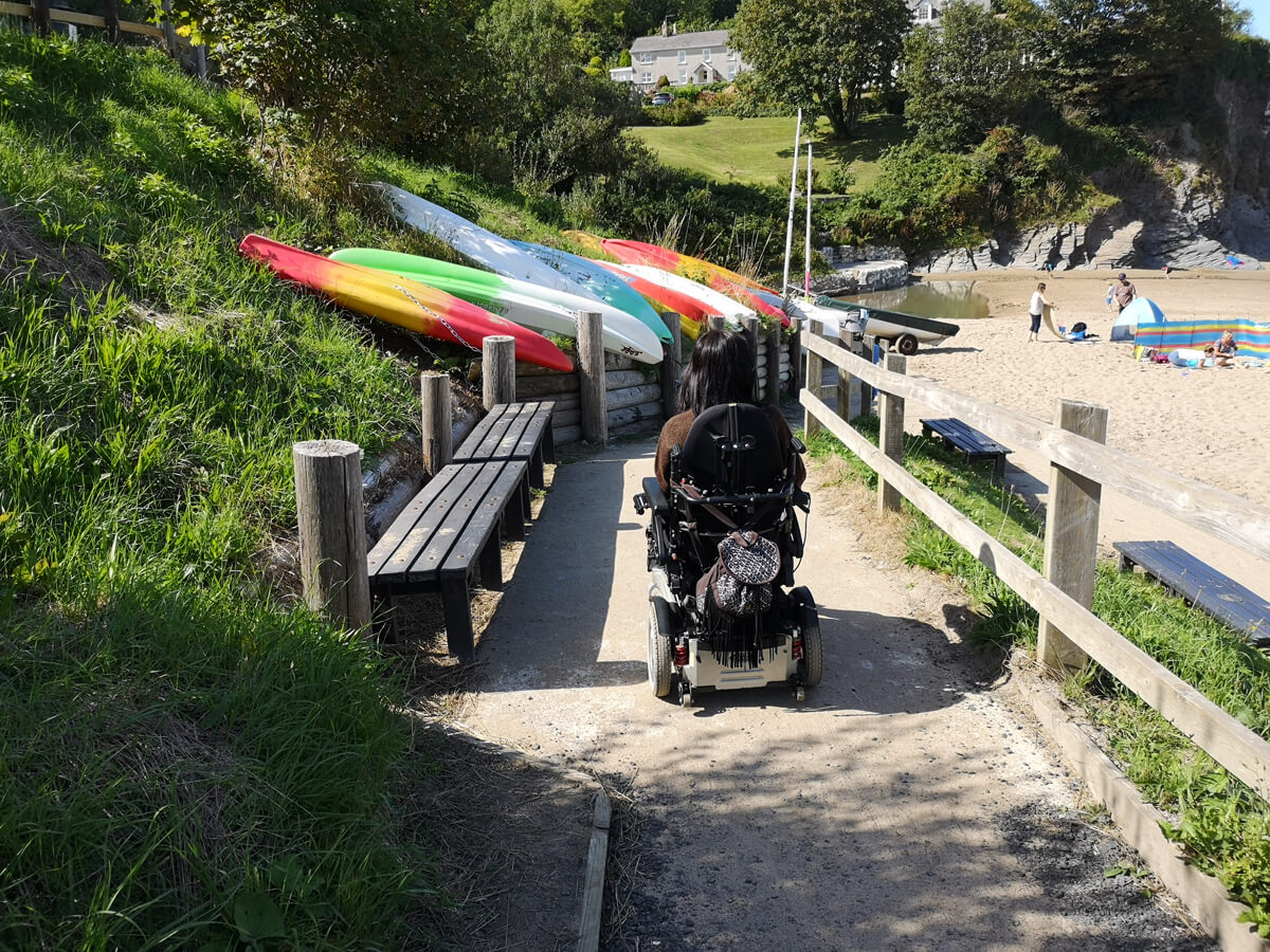 Emma driving her wheelchair down the ramp to the beach level at Aberporth.