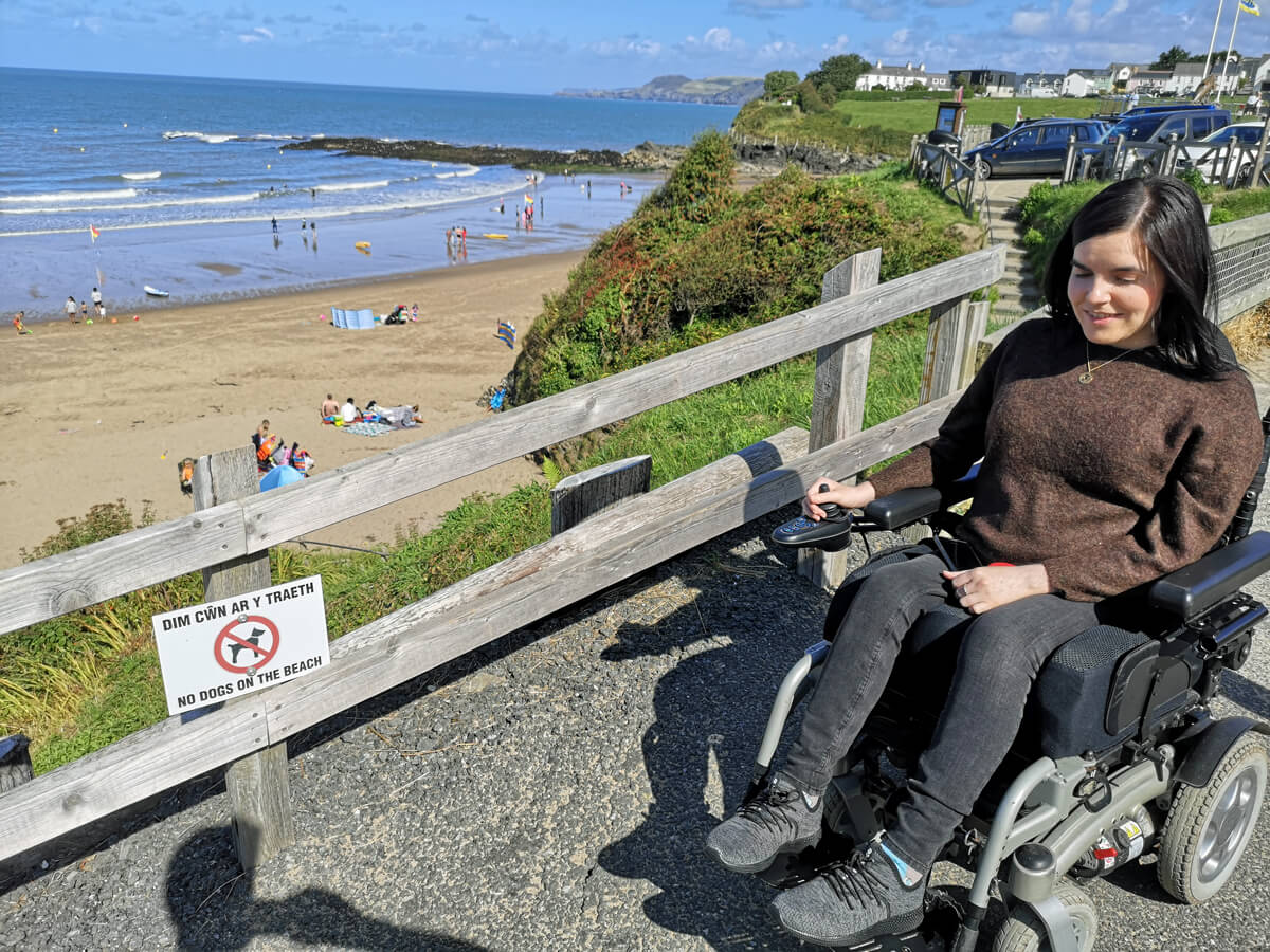 Emma sitting in her wheelchair driving down the ramp at Aberporth Beach.
