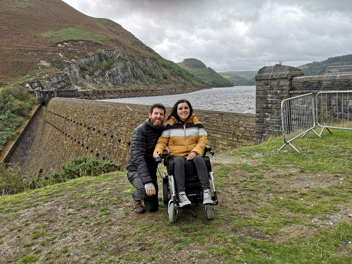 Emma and Allan smiling with the Elan Valley dam behind them.
