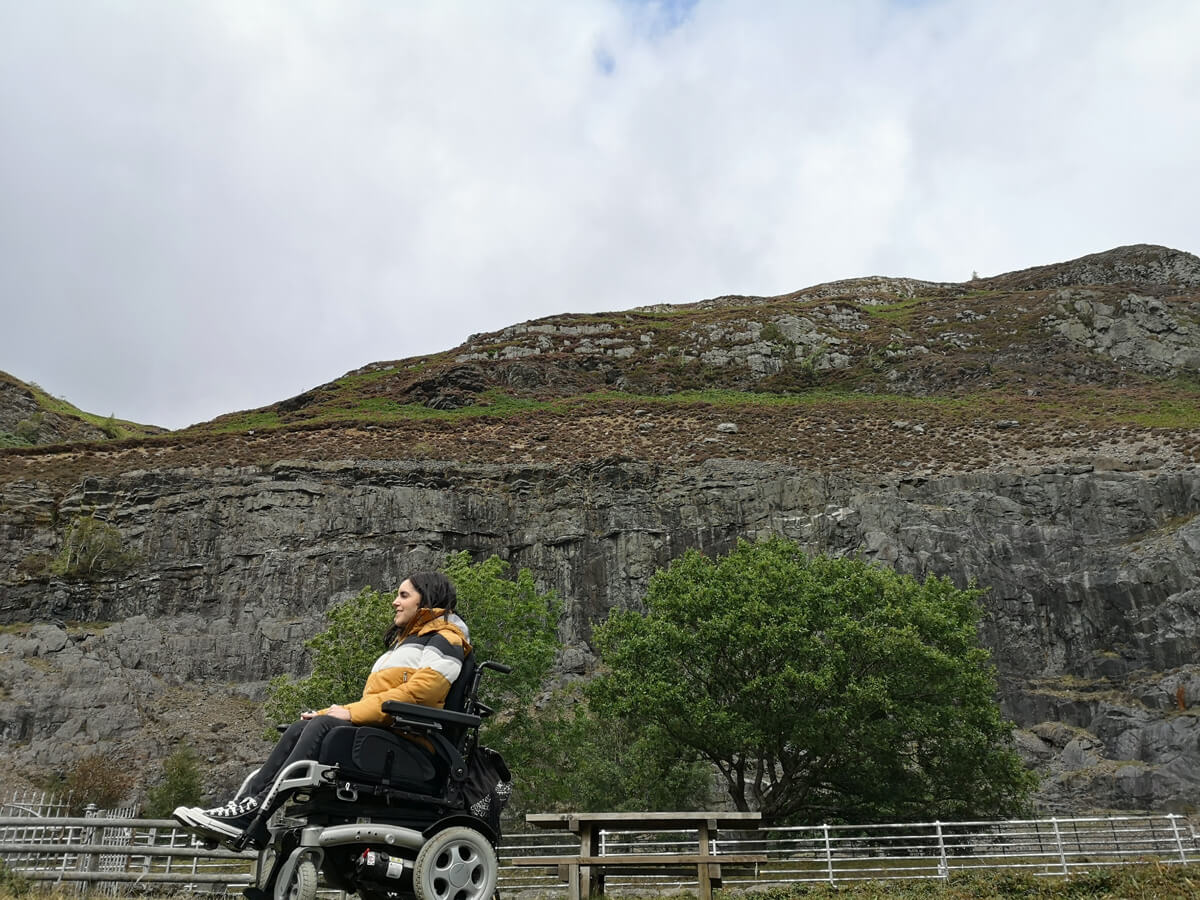 A side view of Emma and her wheelchair with the mountain rocks behind her.