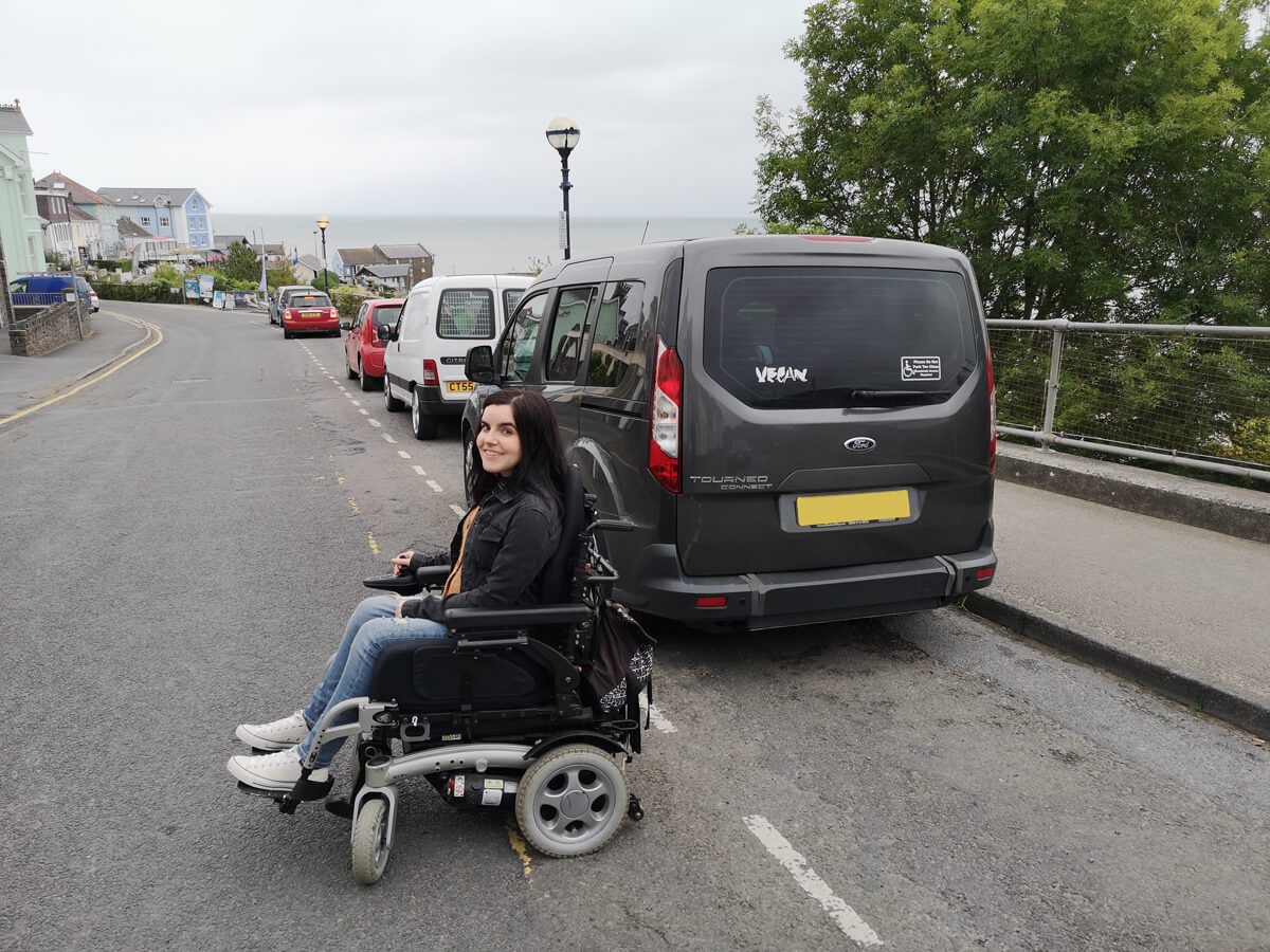 Emma sitting next to her wheelchair accessible car in New Quay, Wale.