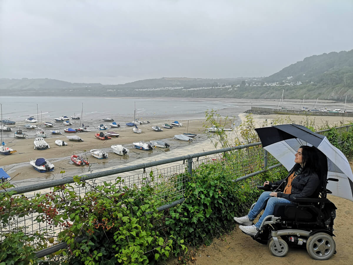 Emma looking at the view of New Quay beach. Emma is holding an umbrella.