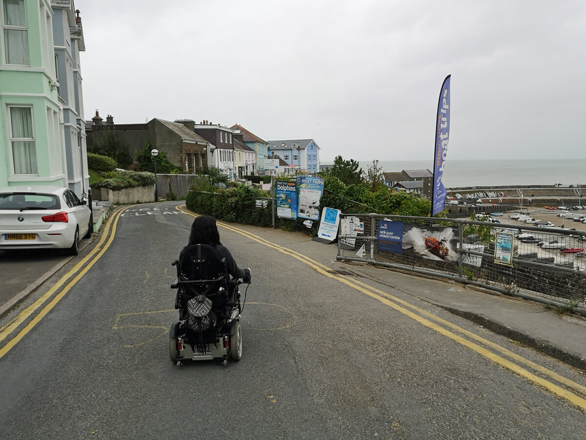 Emma driving her wheelchair down the road towards New Quay beach, Wales