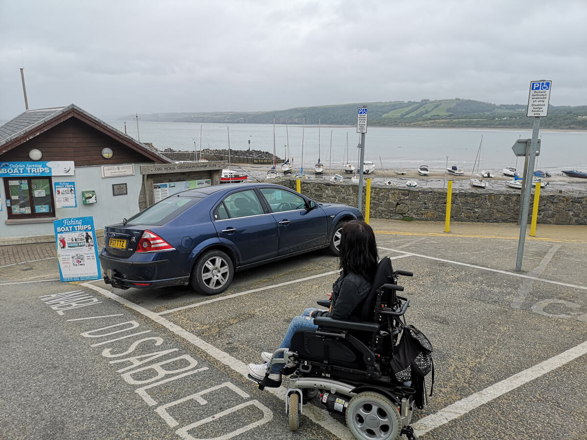 Emma driving across a disabled parking bay in her wheelchair at New Quay beach, Wales.