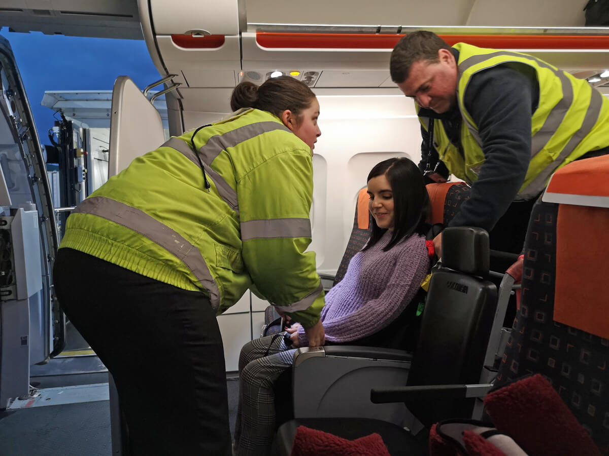 Emma being lifted out of the airplane seat by two special assistance workers.