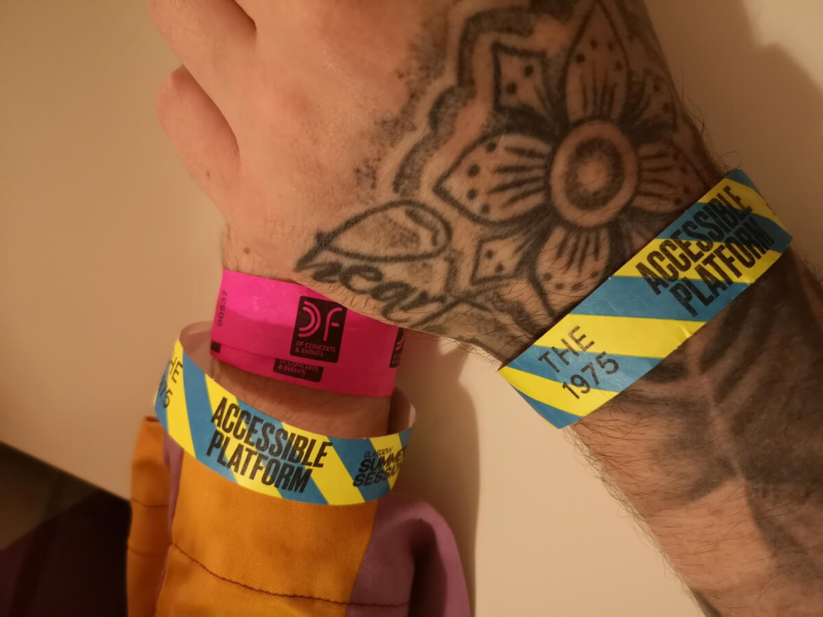 A close up shot of Emma and Allans hands (holding hands) showing their accessible platform wristbands.