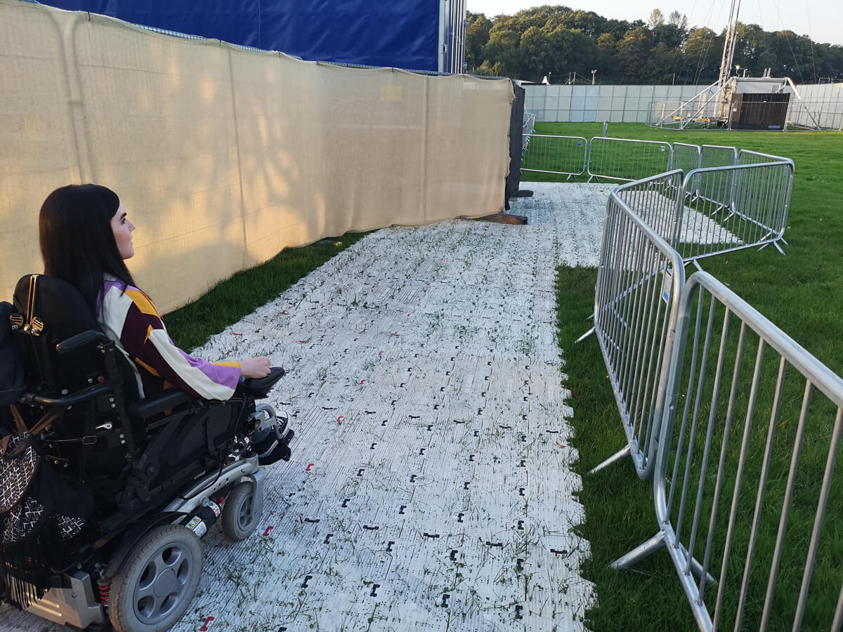 Emma driving across the wheelchair accessible mats laid across the grass.