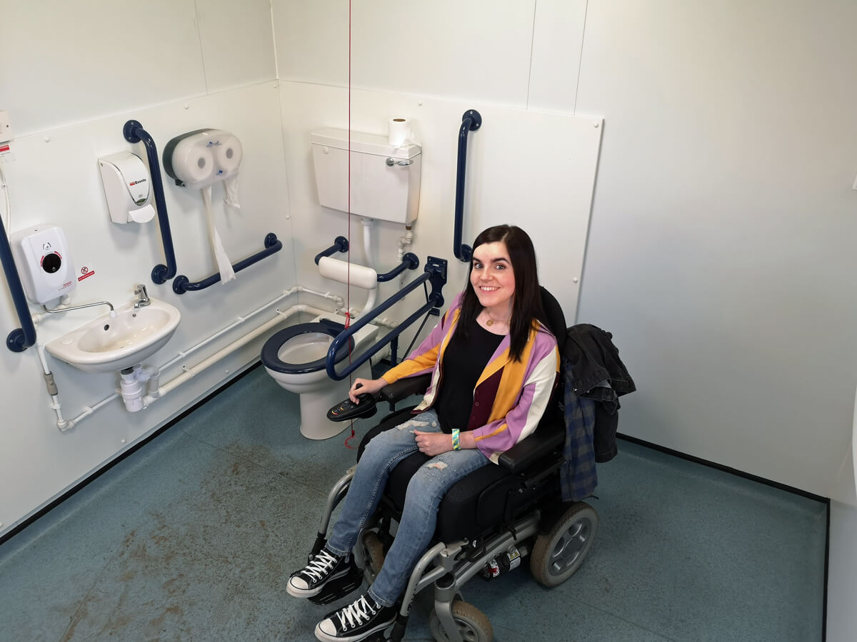 Emma sitting in her wheelchair smiling at the camera while in the large accessible toilet.