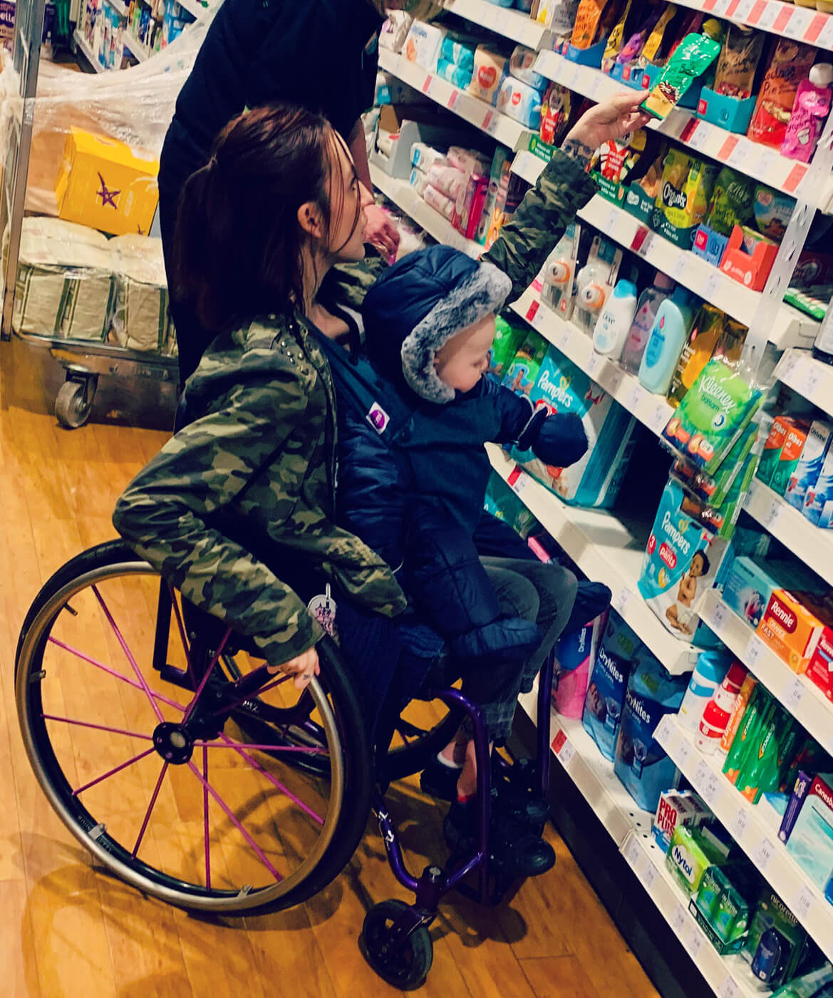 Molly is in her manual wheelchair with her son on her lap. They are in a shop. Molly and Oscar are both reaching for something on the shelf.