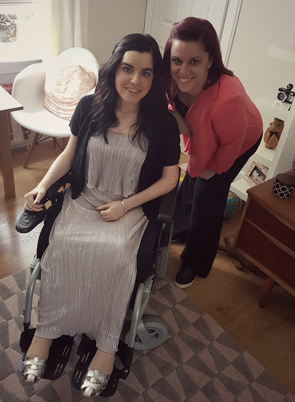 Emma is sitting in her wheelchair. She is wearing a dress. Her sister is standing beside her. They are both smiling.