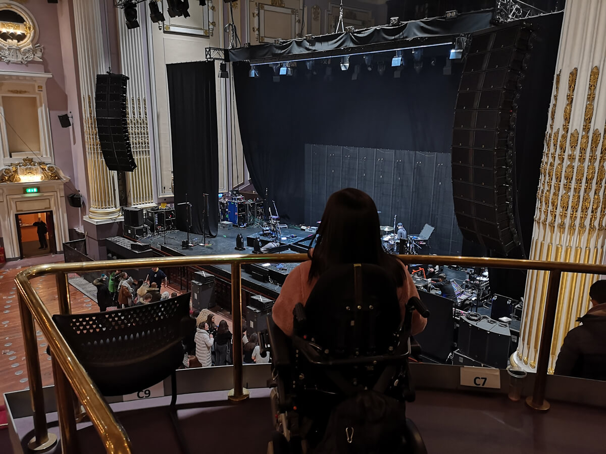 Emma sitting in the wheelchair accessible seating area in the Grand Circle at The Usher Hall.