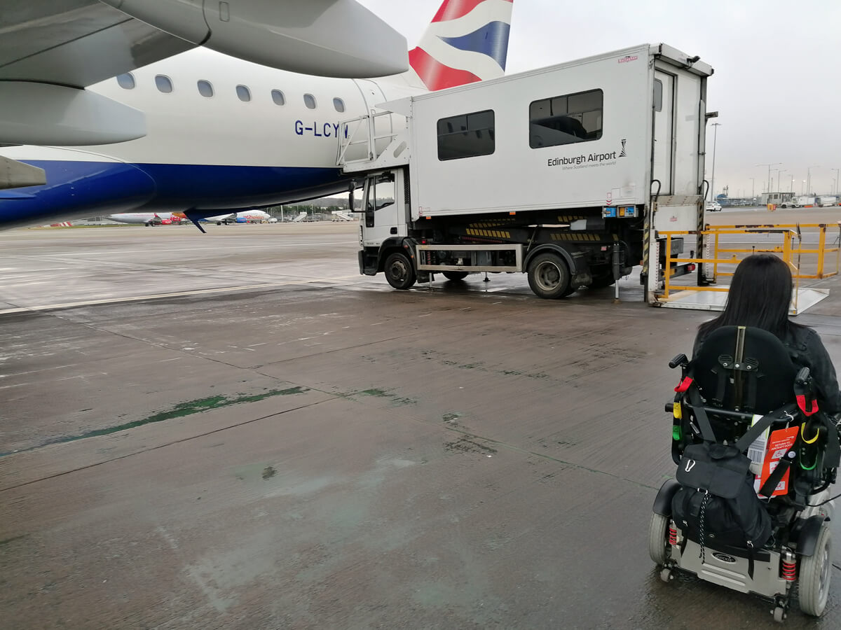 Emma in her wheelchair driving towards the ambulift to board the BA plane which is also in shot.