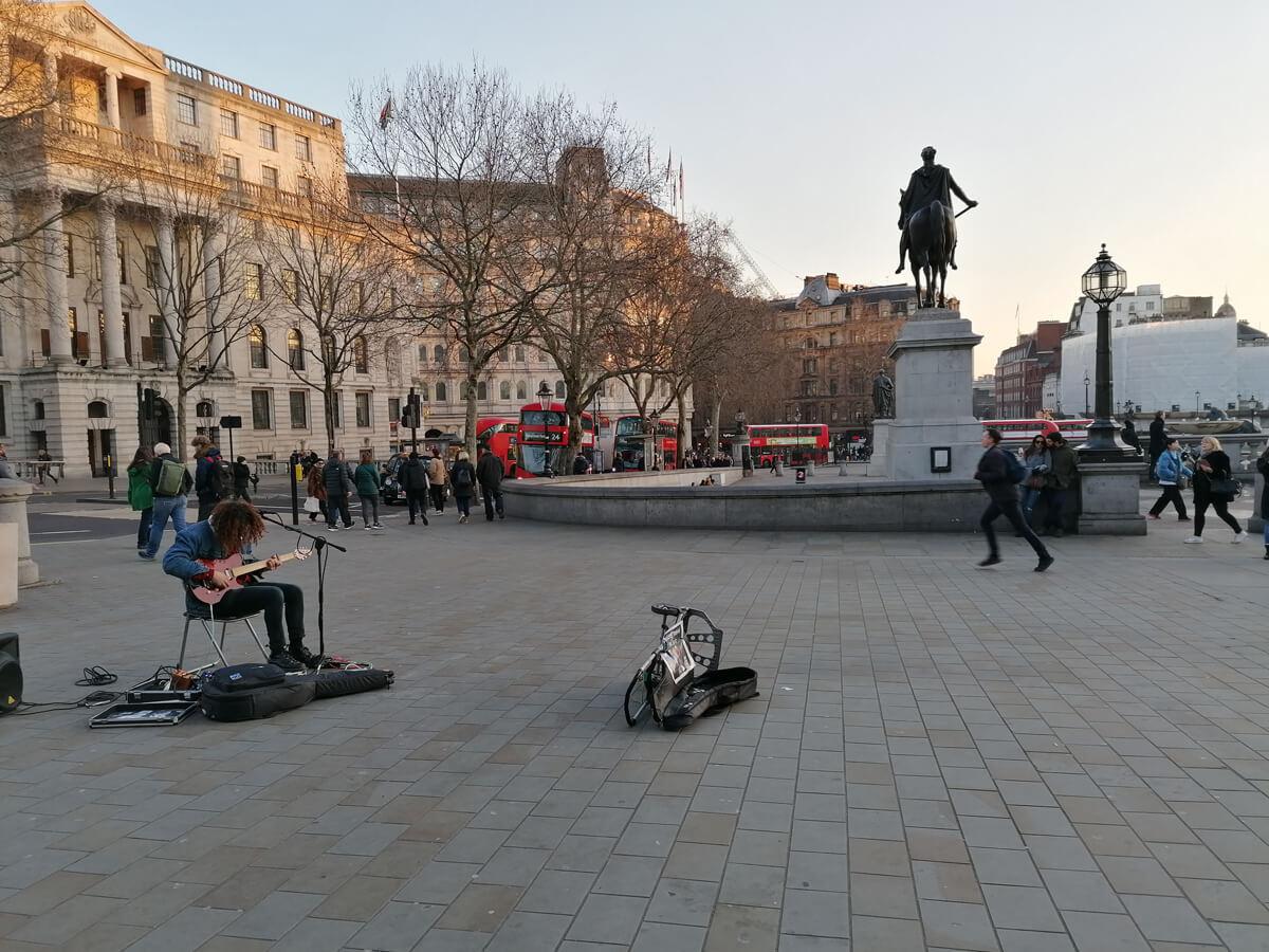 A street musician performing in Trafalgar Street.