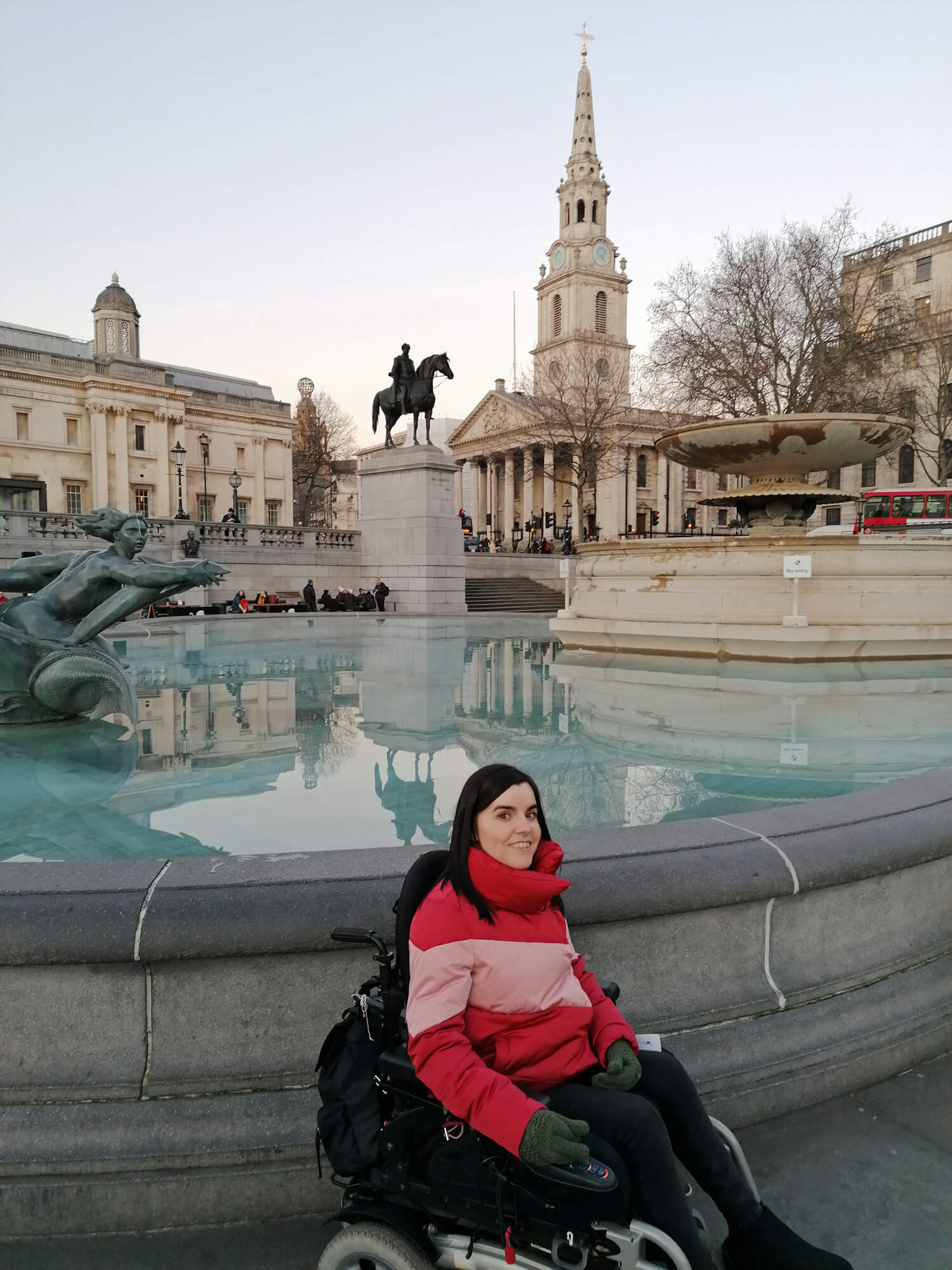 Emma is wearing a red puffy jacket and is sitting next to the Trafalgar Square fountain