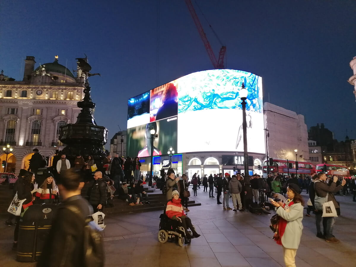 Emma sitting in her wheelchair in the middle ofPiccadilly Circus at night.