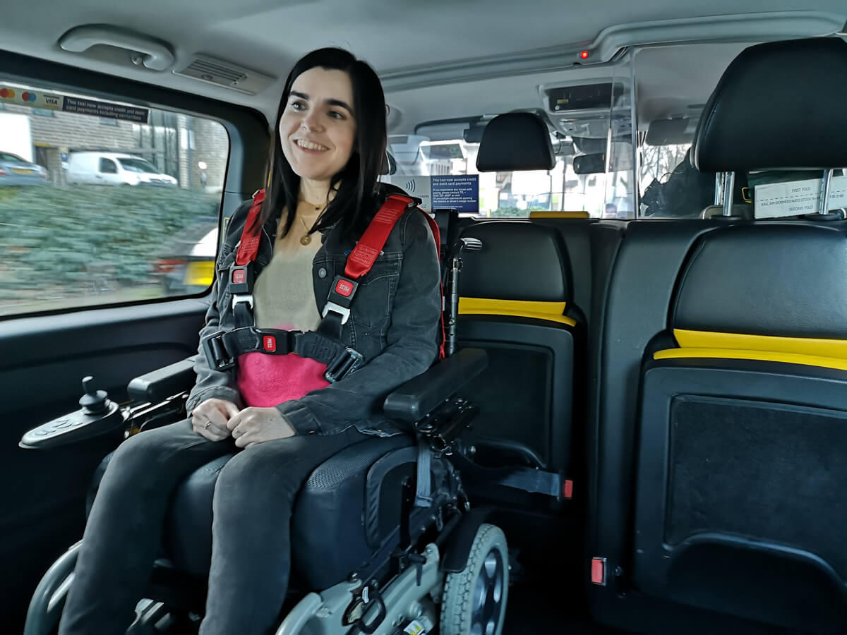 Emma sitting in her wheelchair wearing a harness seat belt in the back of a taxi.